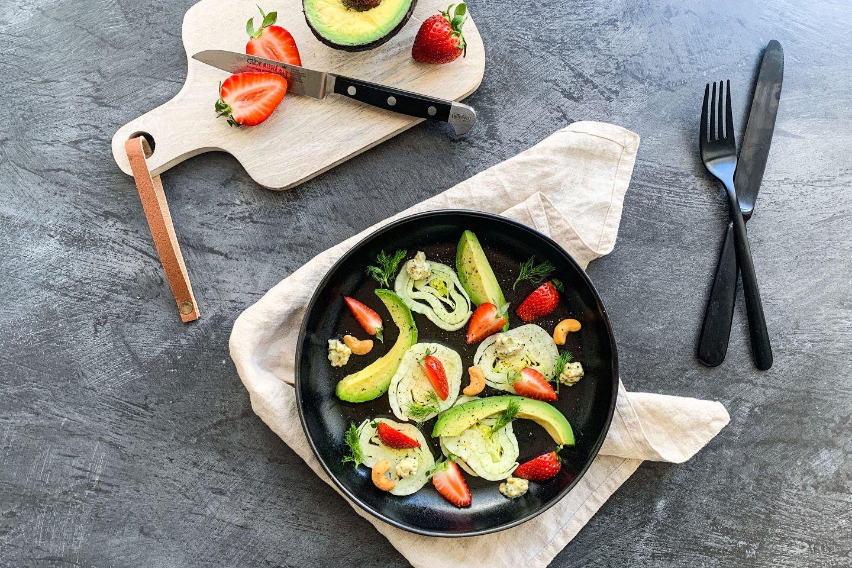 Avocado-Fenchel-Salat mit Kokosdressing in einem tiefen, schwarzen Teller neben einem Brettchen mit Erdbeeren und Avocado