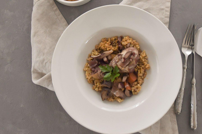 Coq Au Vin auf Einkornreis in einem tiefen Teller, dazu ein Schälchen mit Gemüse in Sauce auf grauem Untergrund