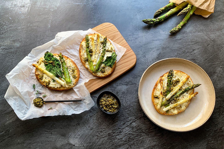 3 Naan Pizzen mit Spargel belegt auf einem Holzbrettchen und einem Teller angerichtet