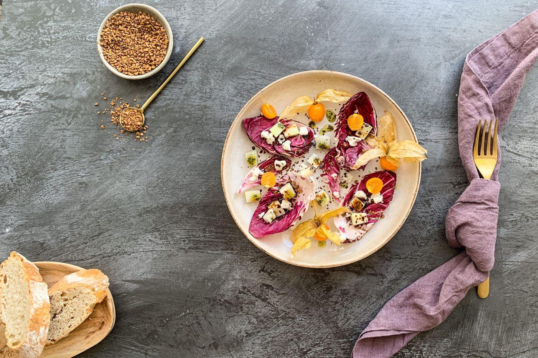 Radicchio Salat mit Kohlrabischeiben und Physalis auf einem beigen Teller mit Brot und Serviette angerichtet