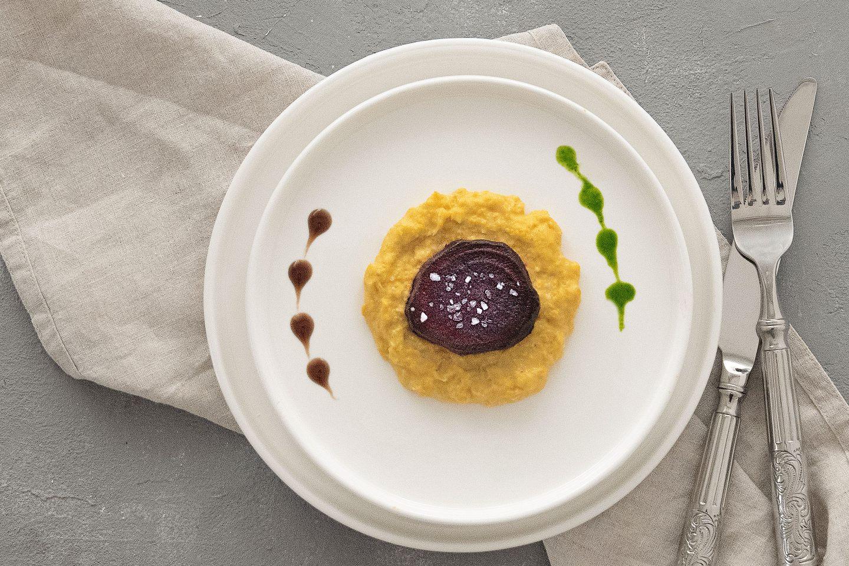 Rote Ruebe auf maispüree mit etwas grüner Sauce und Balsamico Essig auf einem weißen Teller