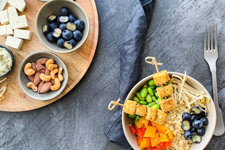 Quinoa-Bowl mit frittierten Tofu-Würfeln, Nüssen und Heidelbeeren in einer Schale angerichtet