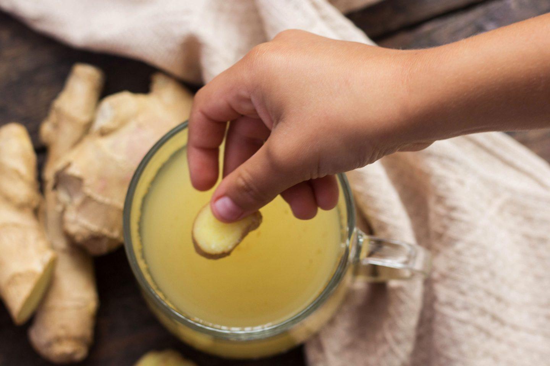 eine Frauenhand gibt ein Ingwerstück in eine Karaffe