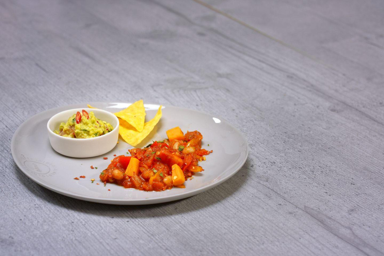 Chili Mit Suesskartoffeln und Guacamole in einem Schälchen sow Tortillachips
