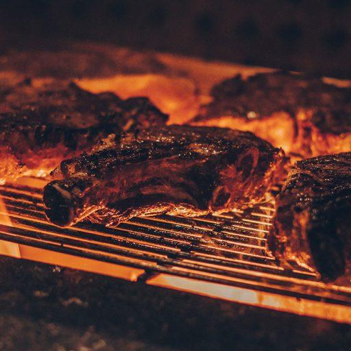 Gewürztes Fleisch wird über Feuer gegrillt
