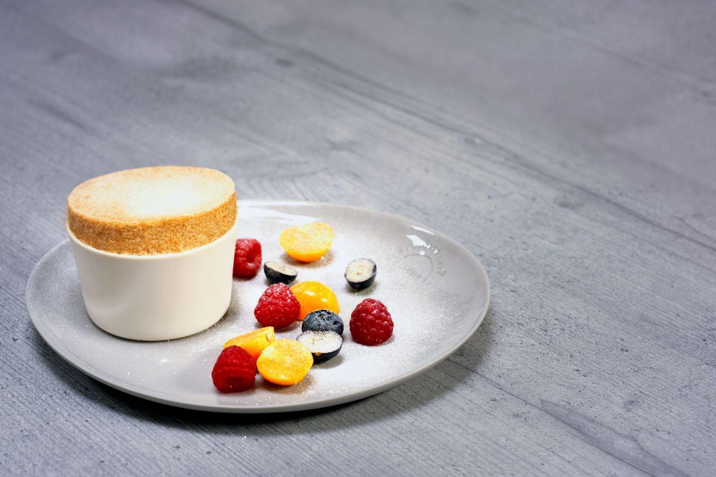 weiße Schookolade-Lebkuchen Souffle mit Staubzucker gezuckert und frischen Beeren und Physalis garniert