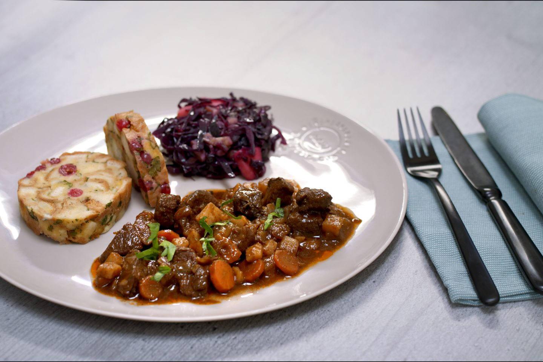 Rehragout mit Rotkraut und Ribisel-Serviettenknoedel auf einem beigen Teller mit schwarzem Besteck
