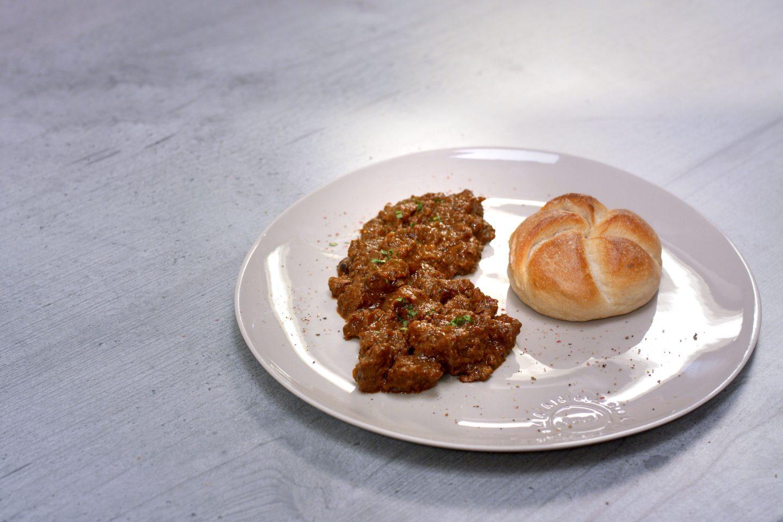 Schawarzbiergulasch mit einer Semmel auf einem gräulichen Teller