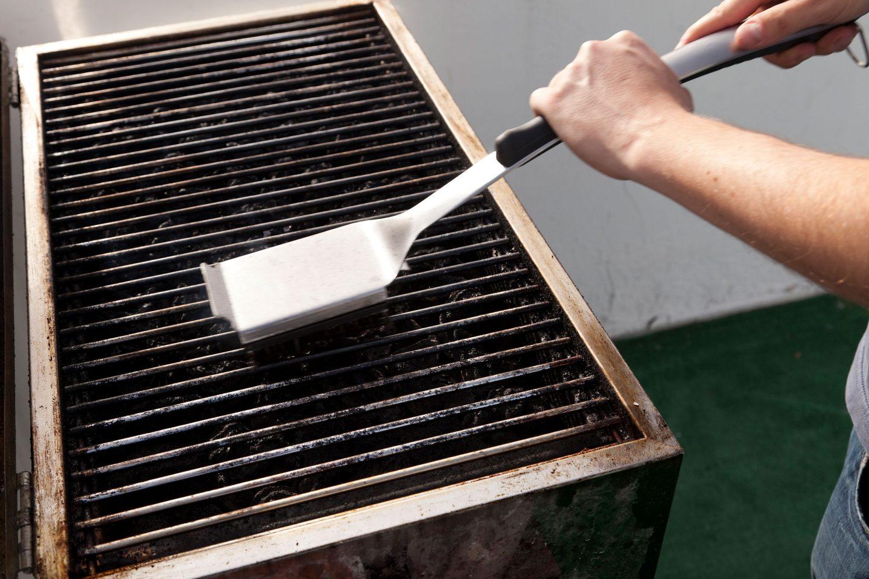 MAnn reinigt Griller mit einer Grillbürste
