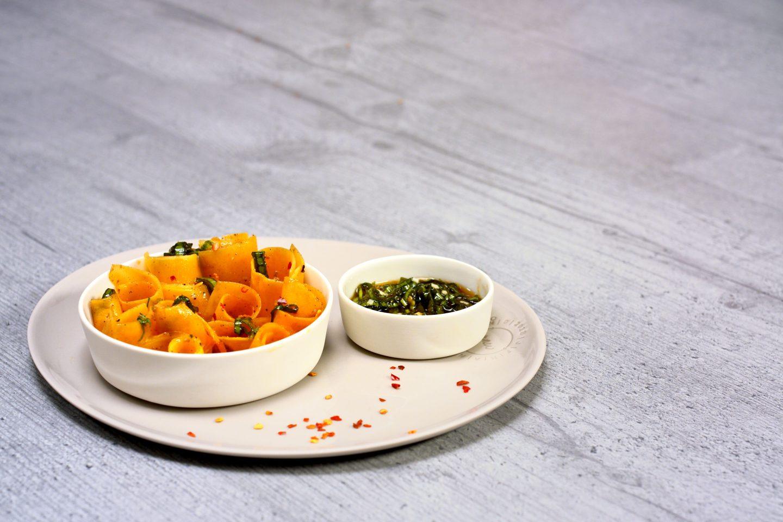 Kuerbissalat mit würzigem Dressing in 2 Schälchen auf einem Teller