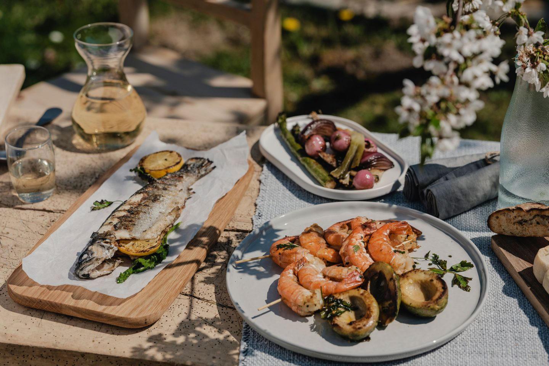 verschiedene Grillgerichte von Forelle bis Grillgemüse und Shrimp-Spieß auf einem Holztisch im Garten