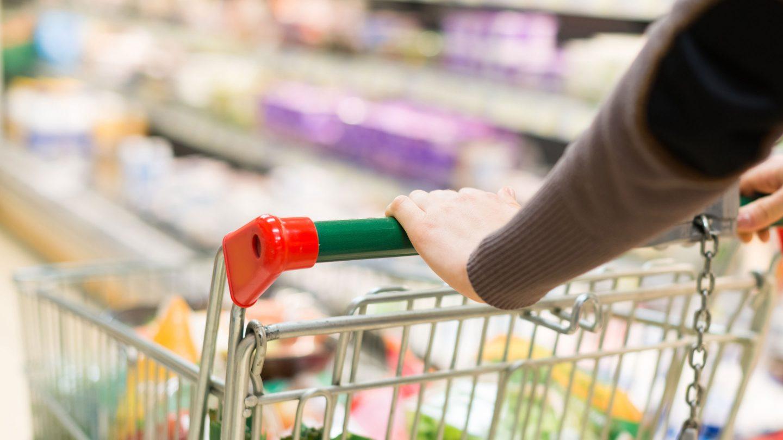 Foto: ein Einkaufswagen wird den Supermarktgang entlang geschoben