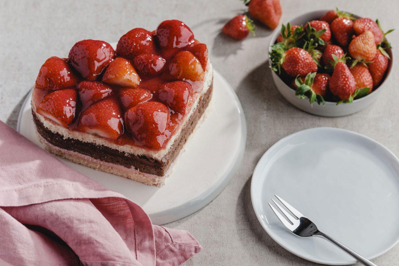 Erdbeer-Schokokuchen in Herzform und ein Schälchen mit Erdbeeren sowie Serviettte und Teller mit Kuchengabel