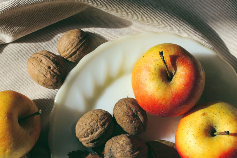Äpfel und Walnüsse auf einem weißen Teller
