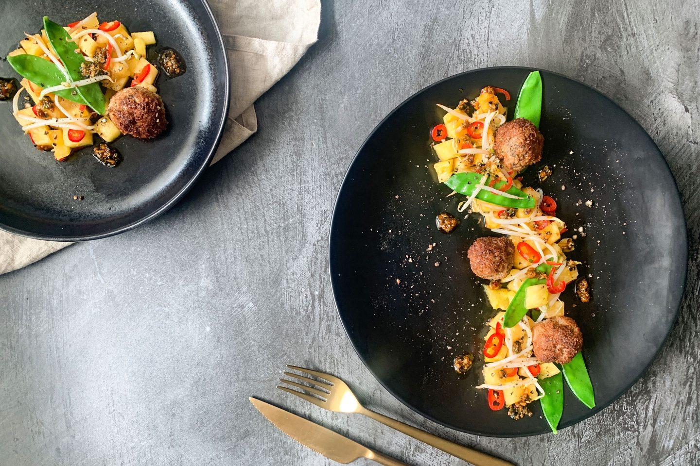 Foto: Salat mit frischen Erbsenschoten, frittierten Kokos-Huhn-Bällchen und Ananas auf einem schwarzen Teller mit goldenem Besteck angerichtet