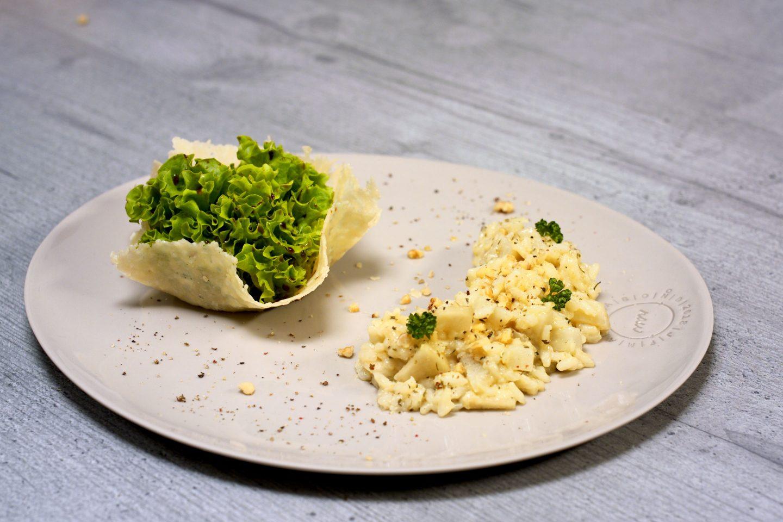 Topinambur Risotto mit Birne auf einem Teller mit Salat in einem Parmesanbecher