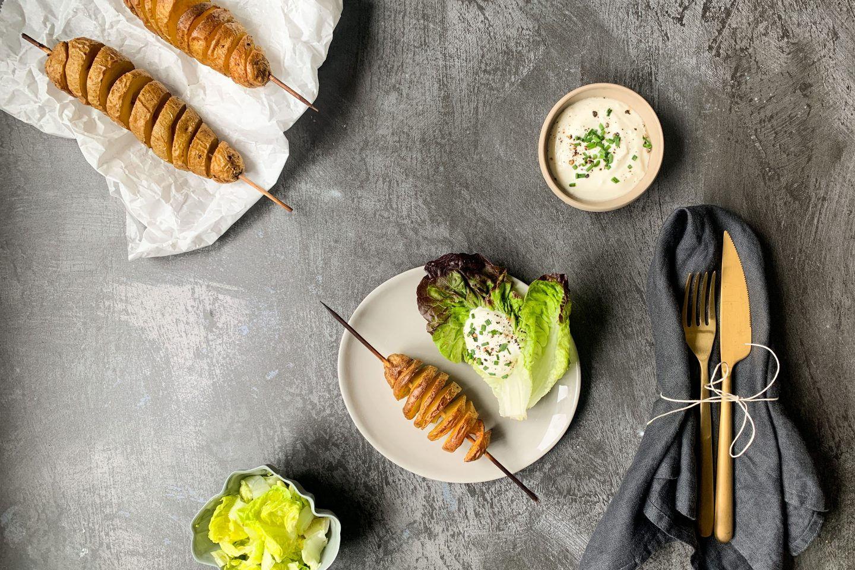 Foto: Spiral-Kartoffeln auf Holzspießen mit Salatgarnitur und Sour Cream, mit goldenem Besteck, grauer Serviette auf dunkelgrauem Untergrund
