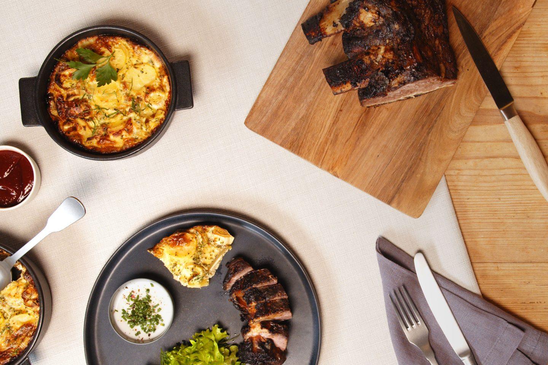 ein dunkler Teller mit aufgeschnittenen Beef Ribs und etwas Kartoffelgratin sowie Salatbeilage auf einer hellgrauen Tischdecke