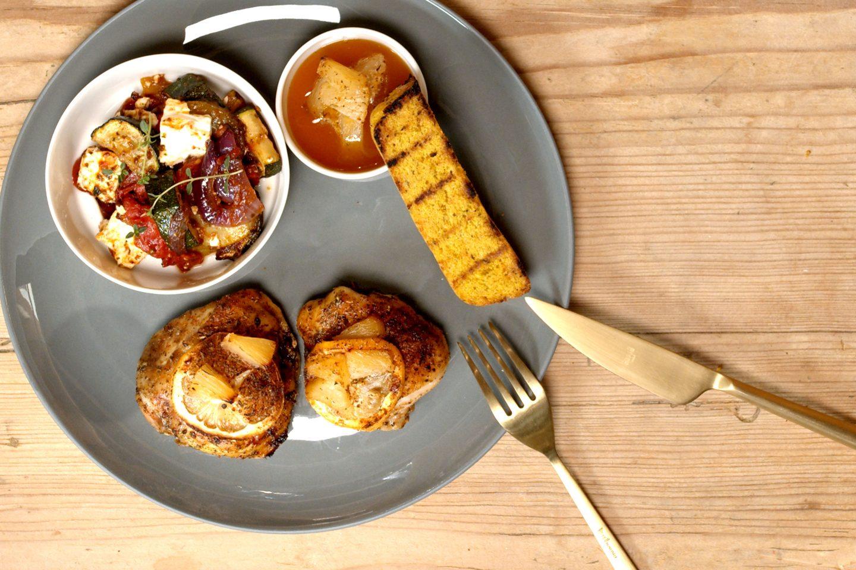 Huhn Hawaii Style mit gegrilltem Polentasterz auf einem dunkelgrauen Teller mit einem Schälchen voller Ratatouille, mit goldenem Besteck
