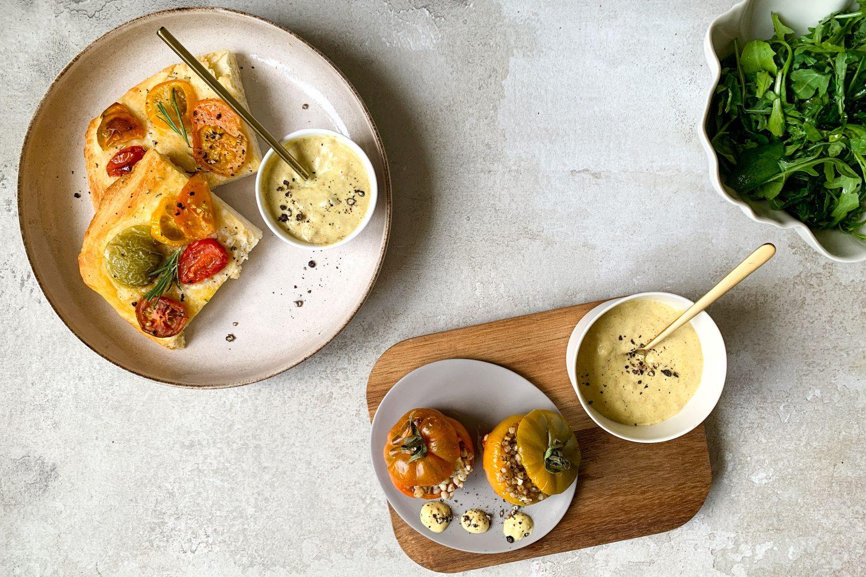 Gefüllte Tomaten auf einem Tellerchen, daneben ein Schälchen mit Curry-Bananen-Dip mit goldenem Löffel auf einem Holzbrett