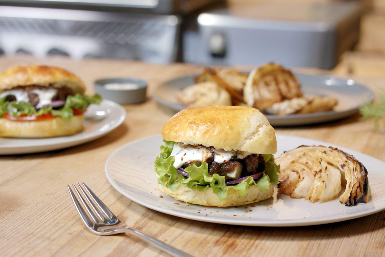 Burger mit Käse-Röstzwiebel-Patty und gegrilltem Krautkopf auf einem hellen Teller auf einem Holztisch