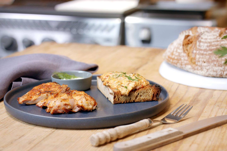 Gegrillte Schweins-Fledermaus aufgeschnitten auf einem grauen Teller mit einem Stück gegrilltem Brot mit überbackenem Aufstrich