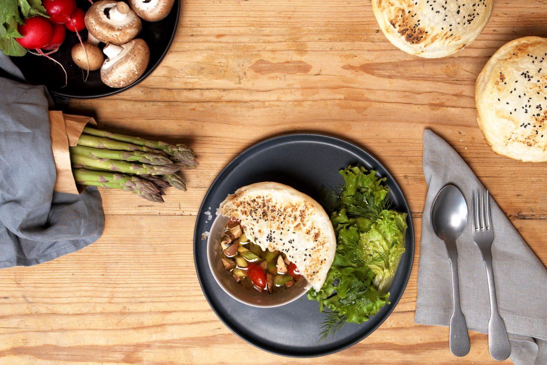 Gemüsebowl mit Blätterteighaube, die halb entfernt wurde auf einem schwarzen Teller auf einem mit frischem Spargel und Pilzen dekorierten Tisch
