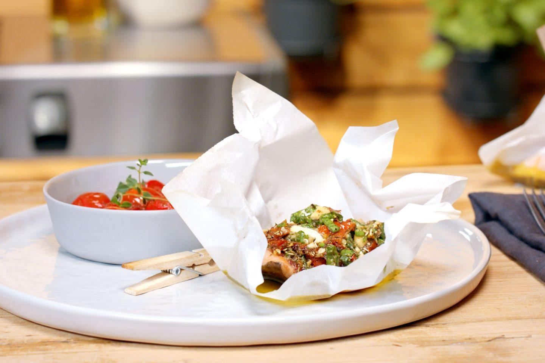 Lachsforelle in einem Tascherl aus Backpapier mit Grill Fisch Grillgewürz, Erdnüssen und Jungzwiebel getoppt, neben einem Schälchen mit Schmelztomaten