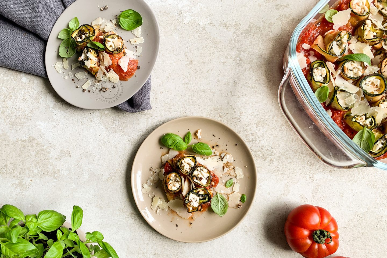 Zucchini-Canelloni auf 2 Tellern und in einer Auflaufform auf einem hellgrauen Untergrund, mit frischem Basilikum und einer Ochsenherztomate