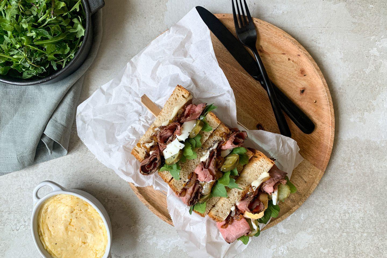 Roastbeef-Sandwich auf Butterbrotpapier auf einem Holzbrett mit schwarzem Besteck und Sauce in einem Schälchen und einem grünen Beilagensalat