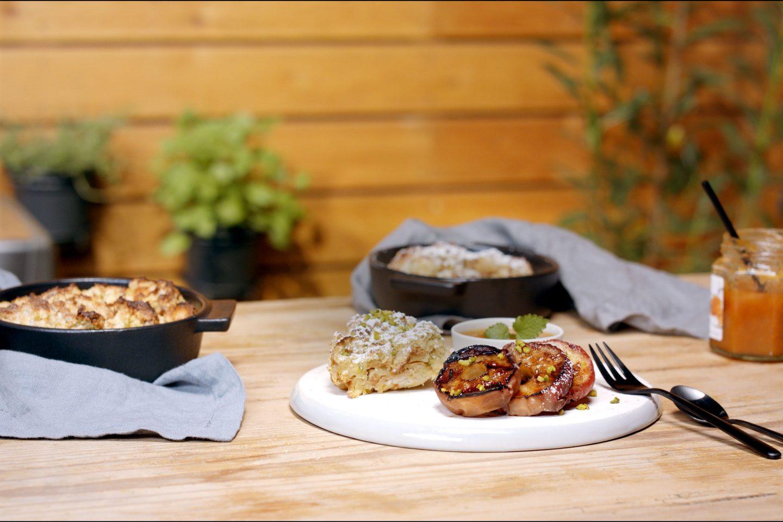 Semmelauflauf aus dem Grill in schwarzen Schälchen; dazu gibt es gegrillte Apfelringe auf einem hellen Teller