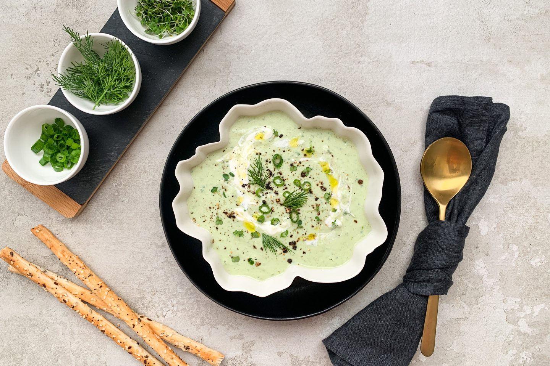kalte Avocado-Gurken-Suppe in einer beigen schale mit Crissini und frischen Kräutern