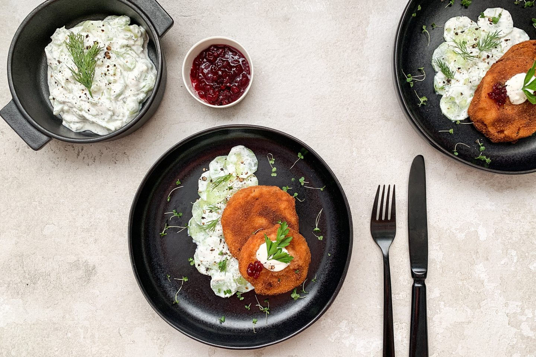 Kohlrabi Schnitzel mit cremigem Gurkensalat auf einem schwarzen Teller mit Preiselbeermarmelade