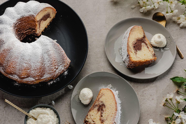 Marmor-Guglhupf auf einem schwarzen Teller und 2 Stück Kuchen auf kleinen Tellern mit Schlagobers, goldenen Gabeln und Apfelblüten