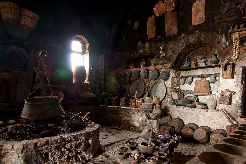 mittelaterliche Küche mit Feuerstelle und zahlreichen alten Kochgegenständen