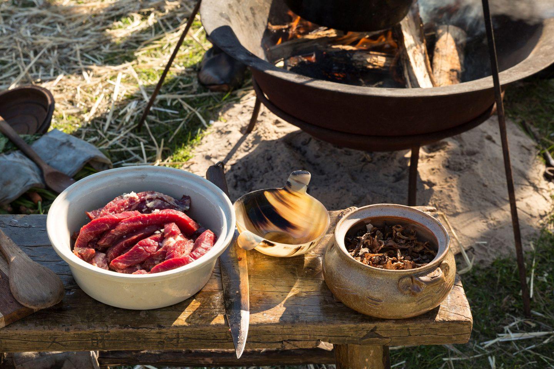 Mittelalterliche Feuerstelle mit Kessel und und einem Bänkchen mit Fleisch und Küchenwerzeug