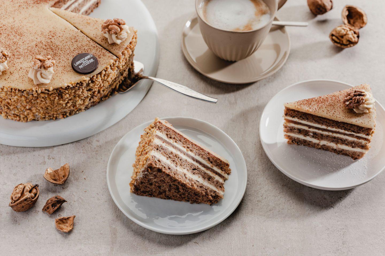 2 Stück Nusstorte mit Haselnusskrokant auf kleinen Tellern mit einer Tasse Cappuccino