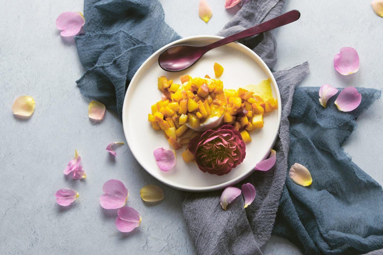 Rosenskyr mit fruchtigen Pfirsichstüchen und Vanillezucker mit Rosenblüte und -blättern auf einem hellen Teller angerichtet