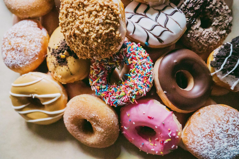 Eine Vielzahl an bunt bestreuten Donuts neben- und übereinander