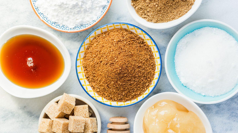 verschiedene Zuckersorten und -alternativen in kleinen Schalen auf Marmoruntergrund