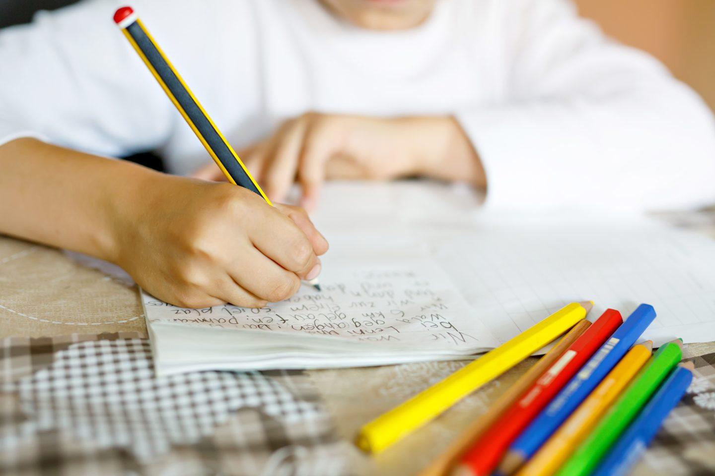 ein Kind schreibt im Unterricht in ein Heft