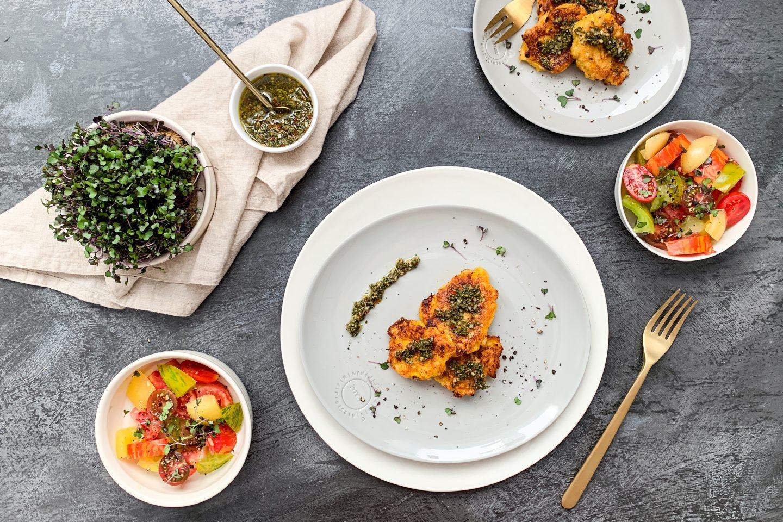 Maispuffer Mit Chimichurri auf hellgrauem Teller mit einem Schälchen Tomatensalat und Kresse