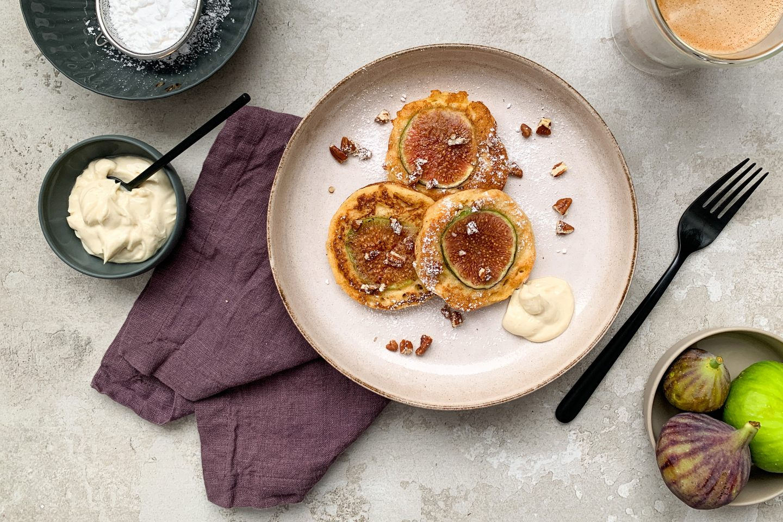 Feigen Pancakes auf einem rustikalen Teller mit Staubzucker, Cardamomcreme und frischen Feigen