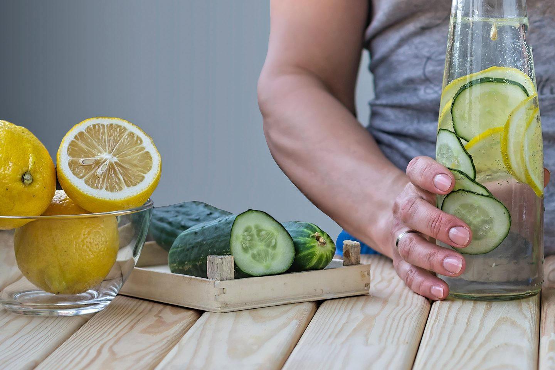 Eine Frau bereitet eine Flasche Wasser mit Gurken- und Zitronenscheiben zu