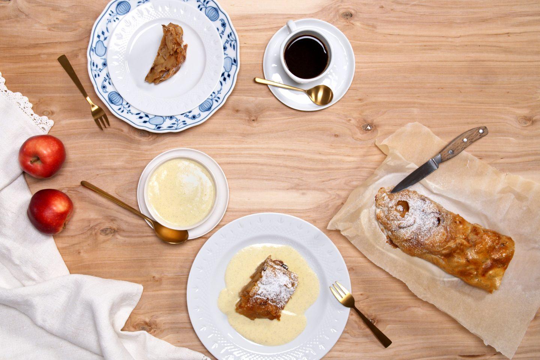 Apfelstrudel Mit Vanillesauce auf 2 Tellern angerichtet mit Kaffe und dem restlichen Apfelstrudel auf Backpapier