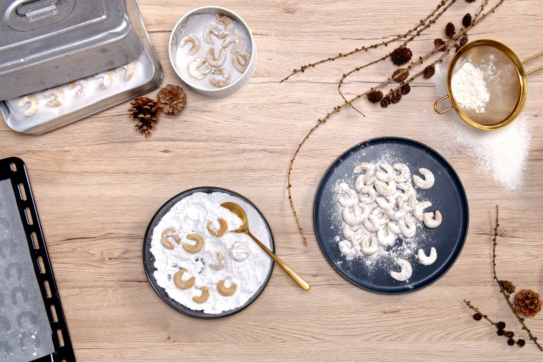 Frisch gebackene Vanillekipferl werden in Vanillezuckergemisch gewälzt und auf einen schwarzen Teller gelegt