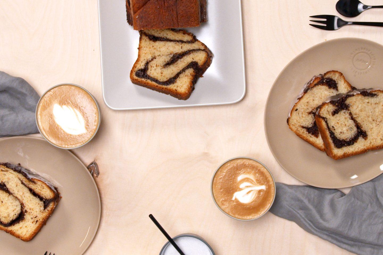 Babka mit Haselnusskrokant und Schokolade auf 2 Tellern mit Cappuccino