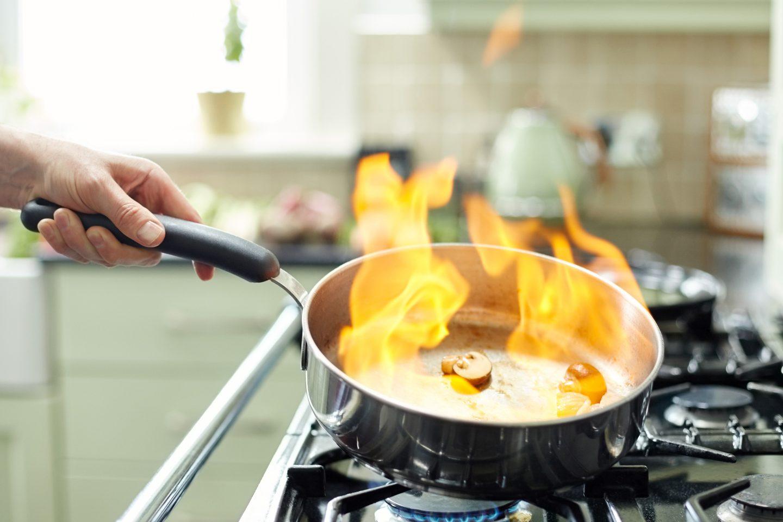 Pilze und Zwiebeln werden in einer Pfanne flambiert