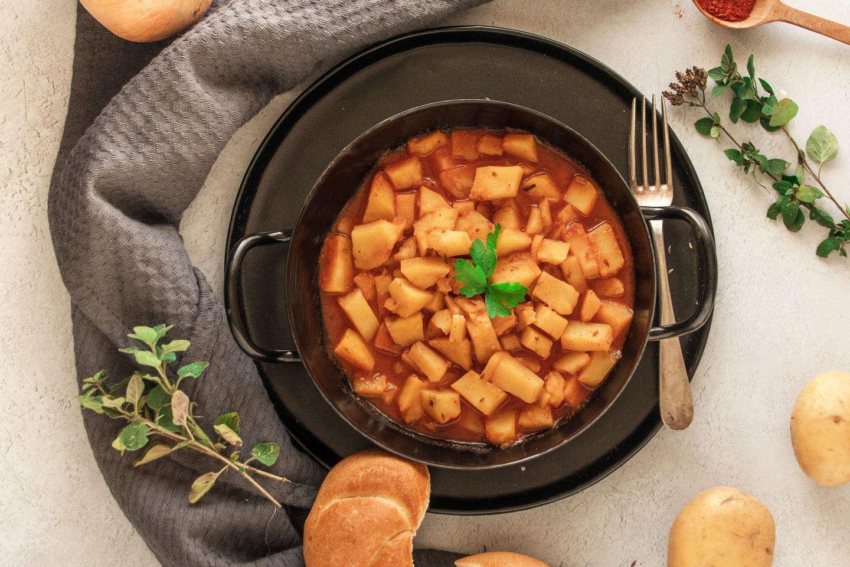 Kartoffelgulasch in einem schwarzen Reindl mit Gabel und Semmel auf einem dunklen Teller
