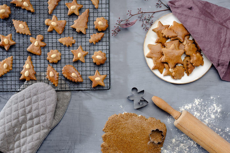 Honiglebkuchen werden gerade aus Teig ausgestochen und liegen zum Abkühlen auf einem schwarzen Kuchengitter